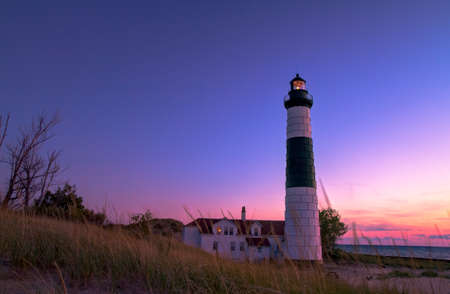 lake michigan lighthouse: El faro de Sable grande como el sol se pone sobre el lago Michigan.