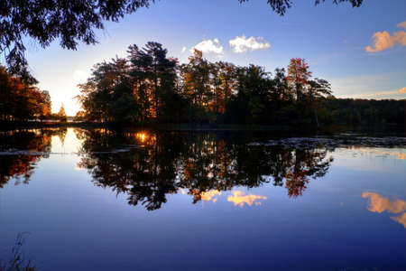ludington: The sunrises behind a forested island creating a mirror image in the still waters of Hamlin Lake. Ludington State Park. Ludington, Michigan. Stock Photo