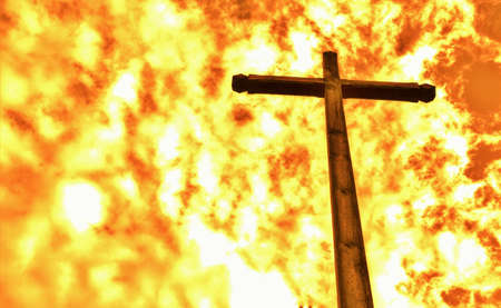 cross: Fireproof. A wooden cross that does not burn set against an inferno. Stock Photo