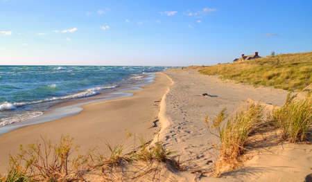 ludington: Coastal Living. A sandy beach with the top of a home rising above the sand dune in the background. (This is not a private residence. But is a public building in Ludington State Park.) Stock Photo