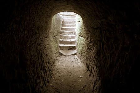 tumbas: Fuera de la oscuridad. Sitio oscuro de piedra con una escalera encerrada en la luz del sol. Foto de archivo
