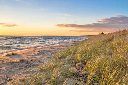 Sunset Beach. The sunsets on a sandy beach bathed in the golden rays of the setting sun. Stock Photo