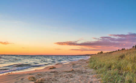 Sunset Beach. De zonsondergangen op een zandstrand badend in de gouden stralen van de ondergaande zon. Stockfoto