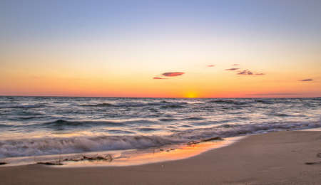 Sunset Beach. The sunsets on a sandy beach bathed in the golden rays of the setting sun.
