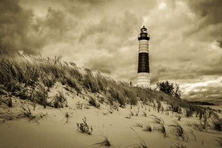 lake michigan lighthouse: El faro de Big Sable rodeado de dunas de arena y un cielo oscuro. Parque Estatal de Ludington. Ludington, Michigan.