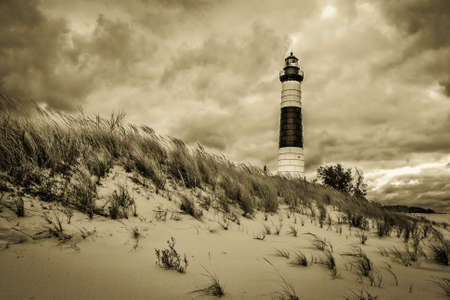 The Big Sable Lighthouse surrounded by sand dunes and a dark sky. Ludington  State Park. Ludington, Michigan. Stock Photo
