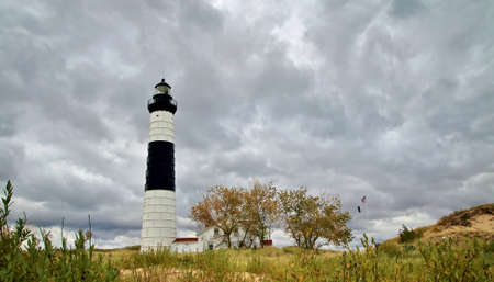 ludington: The Big Sable Lighthouse surrounded by sand dunes and a dark sky. Ludington  State Park. Ludington, Michigan. Stock Photo