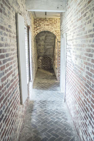 The Dark Passage. Narrow brick hallway with a dark exit at the end. photo