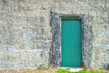 hovel: What Lies Within. Crumbling exterior cement wall with door and copy space. Stock Photo