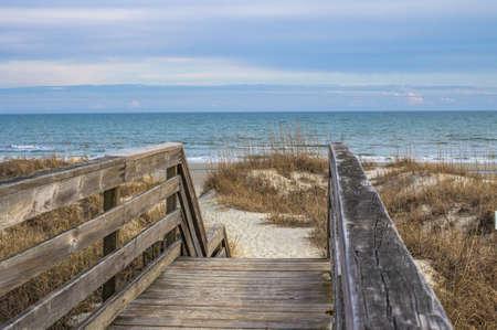 Escape To The Beach. Versleten houten trap leidt naar de Atlantische Oceaan.