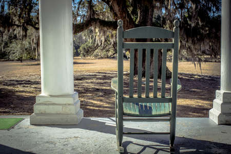antique chair: Southern Afternoon. Wooden rocker on a plantation style home with a Live Oak in the front yard. Stock Photo