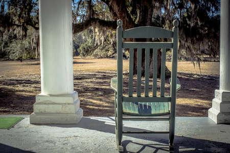Southern Middag. Houten rocker op een plantage stijl huis met een Live Oak in de voortuin.