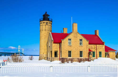 mackinac: Frozen Great Lakes Coast. The Mackinaw Point Lighthouse with the Mackinac Bridge and a frozen Lake Huron as the backdrop.
