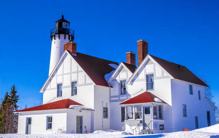 lake dwelling: The Point Iroquois Lighthouse in the Hiawatha National Forest.  This lighthouse is owned  by the US government located on public lands. It is a historical display and not private property. Stock Photo