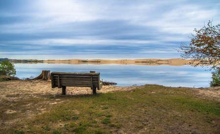 Eenzaamheid. Enkele bank in het park aan de oevers van het toepasselijk genaamde Silver Lake. Silver Lake State Park. Mears, Michigan.
