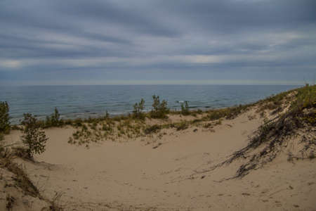 silver state: Moody Lake Michigan. Sand dunes and storm clouds on the horizon. Silver Lake State Park. Mears, Michigan. Stock Photo