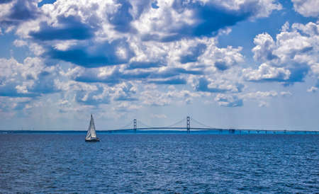 mackinac: Sailing The Straits. Sailboat sailing the Straits Of Mackinaw with the famous Mackinaw Bridge in the background.