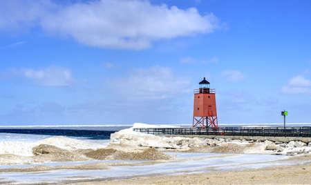 lake michigan lighthouse: Deshielo de la primavera. Nieve deja paso a la arena como la primavera llega a los Grandes Lagos con el Faro de Charlevoix como tel�n de fondo. Charlevoix, Michigan.