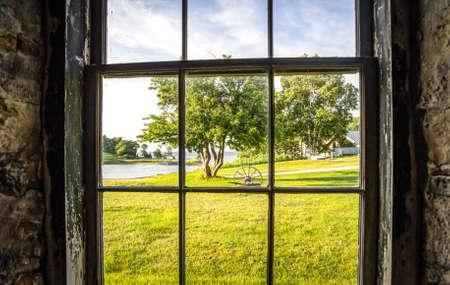 adentro y afuera: Desde fuera mirando hacia adentro. Mirando por la ventana resistida y llevada en una escena rural del pa�s. Foto de archivo