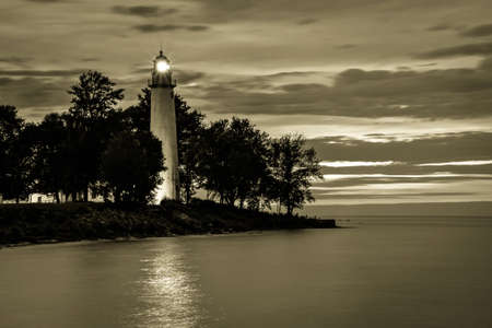 navigational light: Lake Huron Lighthouse. Point Aux Barques Lighthouse beacon shines over the Lake Huron coast. The light remains an active navigational beacon and has been guiding mariners home for over a century. Stock Photo