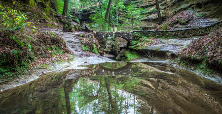 canyon walls: Enchanted Forest Scene. Brick footbridge over stream surrounded by the canyon walls of Hocking Hills State Park. Logan, Ohio