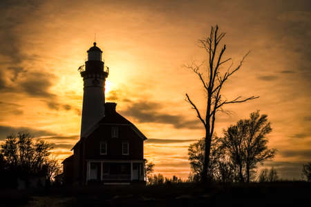 pictured: Au Sable Light Sunset. The silhouette of the Au Sable Lighthouse located in Pictured Rocks National Lakeshore. Munising Michigan.