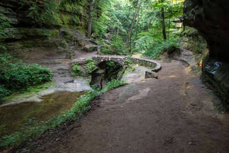The Devils Bridge. Stone footbridge crosses over a ravine dubbed the Devils Bathtub. This magical forest scene is located in Hocking Hills State Park in Logan, Ohio.