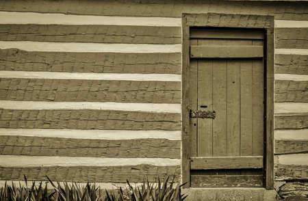 Pioneer Log Cabin. Front door and exterior wall of a pioneer log cabin.