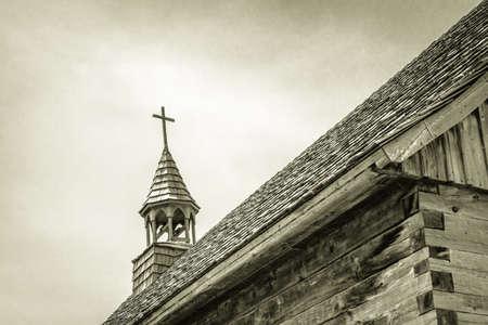 De oude houten kruis. Torenspits van een historische houten kerk in zwart en wit.
