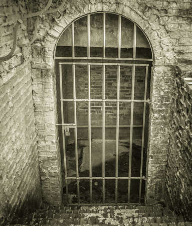 locked: Fear. Stone stairs lead to a locked dungeon style cell with a dirty cement floor. Stock Photo
