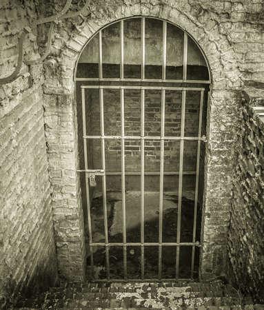 Un escalier en pierre mènent à une cellule verrouillée de style donjon avec