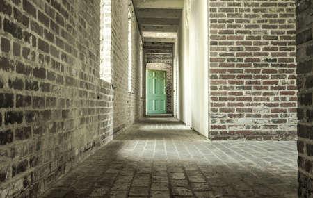 perspective room: Behind Closed Doors. Weathered brick corridor with wooden door.