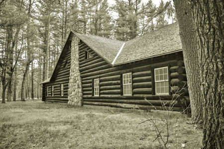 grayling: Historical Log Cabin. Exterior wall and chimney of historical log cabin built by the CCC in the 1930s. Hartwick Pines State Park. Grayling, Michigan. This is a public building located on public lands and is not a private residence.
