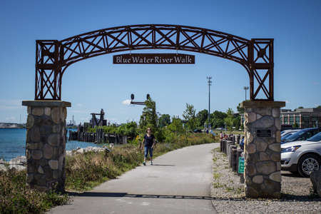 encompasses: Blue Water River Walk. Port Huron, Michigan, USA - June 9, 2015. The Blue Water Riverwalk on a sunny summer day. The Riverwalk was opened on June 7, 2014 and encompasses almost a mile of shore along the St. Clair River.