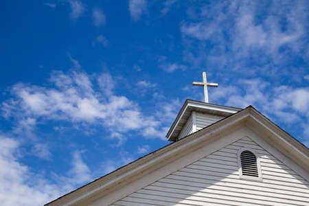 iglesia: Antecedentes Cruz de madera. Cruz de madera en una torre sencilla frente a un cielo azul soleado de verano.