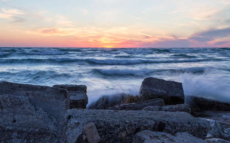 ludington: Dawn Of A New Day. Waves crash on the rocky coast of beautiful Lake Michigan at sunset. Ludington State Park. Ludington, Michigan. Stock Photo