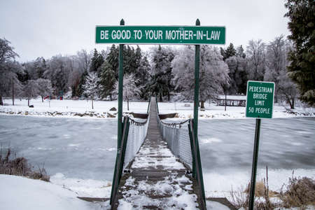 michigan snow: The Swinging Bridge. The swinging footbridge also known as the, Mother-n-Law, bridge is the longest swinging footbridge in the state of Michigan and is located in Croswell, Michigan. Stock Photo