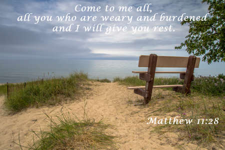 new testament: Rest. Park bench on the beach with stormy sky background and verse from the New Testament. Stock Photo