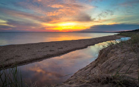 endings: Summer Sunset Background. Sunset on the shores of Lake Michigan with the Brevort River in the foreground.