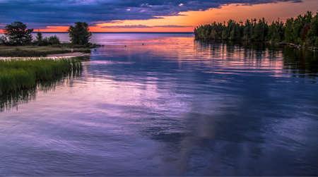 enters: Tahquamenon Sunrise. Sunrise over the Tahquamenon River as it enters Lake Superior. Paradise, Michigan.