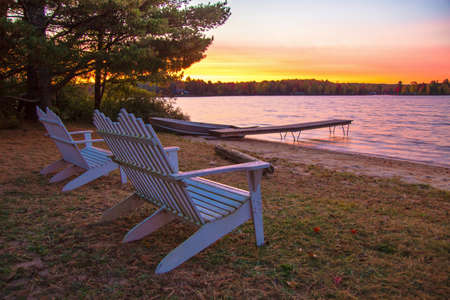 Lakeshore Sunrise. Summer sunrise on the lake with Adirondack chairs and a boat dock.