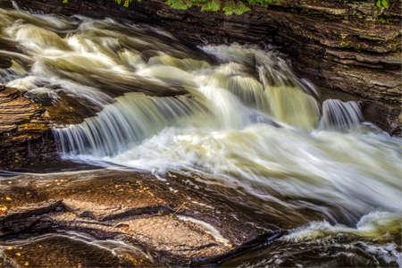 Tahquamenon의 돌진하는 물. 미시간, 낙원의 Tahquamenon 강에서 바위 난간에 물이 몰려 듭니다. 스톡 콘텐츠