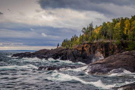 marquette: Lake Superior Coast. Gray sky and stormy seas crash on the cliffs of the black rocks along the shores of the Lake Superior coast. Presque Isle Park. Marquette, Michigan.