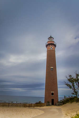 lake michigan lighthouse: Little Sable Point Lighthouse. The Little Sable Point Lighthouse in vertical orientation under stormy gray skies. The Little Sable Light was built in 1874 continues to operate today on the shores of Lake Michigan. Silver Lake State Park. Mears, Michigan. Foto de archivo