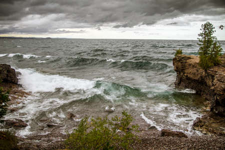 panoramic sky: Storm On The Horizon. Stormy grey skies line the horizon as waves batter the shores of Lake Superior in Presque Isle Park in Marquette, Michigan. Stock Photo