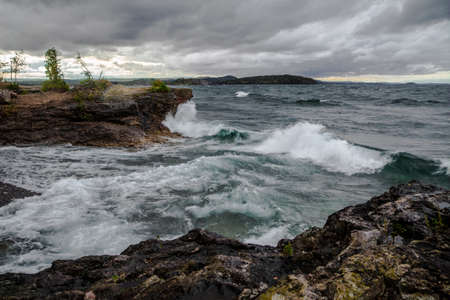 marquette: Wild And Stormy Lake Superior Coast. Lake Superior waves crash on the cliffs of Presque Isle Park in Marquette, Michigan. Referred to as the Inland Sea, Lake Superior is the largest of the five Great Lakes.