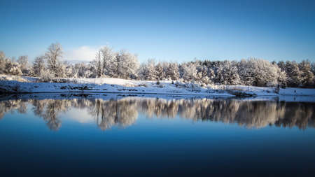 blue christmas: Panoramic Winter Lake Reflections. Snow covered trees reflected in the waters of a small inland lake in the Michigan forest. Shot in panoramic orientation. Stock Photo