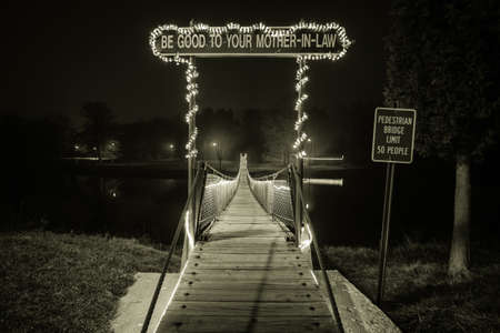 mother in law: The Mother In Law Bridge. The longest swing bridge in Michigan is located at Croswells Swinging Bridge. Known as the Mother In Law Bridge it spans the Black River. This is a public structure in a city park and is not privately owned. Stock Photo