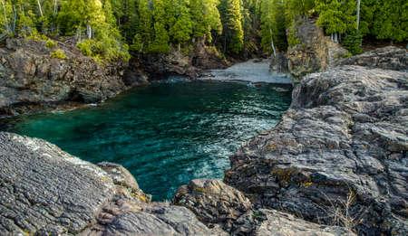 marquette: Lake Superior Cove. The Black Rocks on the shores of Lake Superior are a popular cliff diving location In Marquette, Michigan. The Black Rocks are located in Presque Isle Park. Marquette, Michigan.