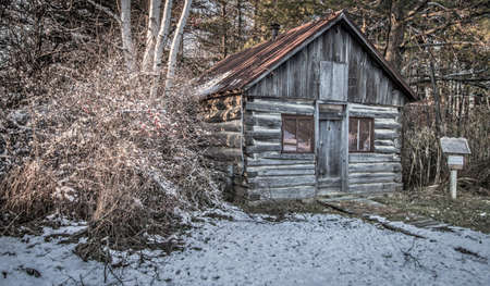 log cabin in snow: Historical Pioneer Log Cabin. Small historical log cabin in the woods surrounded by snow. This is not a privately owned residence, it is located in a historical village as a public display Stock Photo